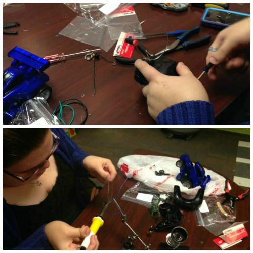 Using a screwdriver to open the remote to a toy car and soldering at DIYAbility.
