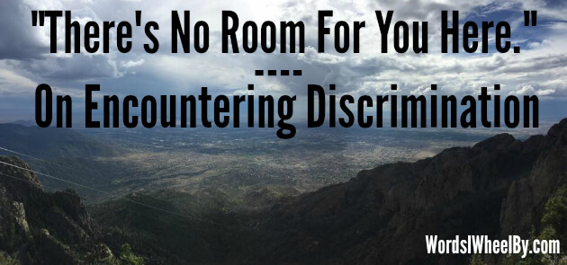 "Image reads ""There's no room for you here. On encountering discrimination."" Text is set against a panoramic photo of a mountain scene below a cloudy sky in Albuquerque, New Mexico."